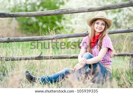 Portrait of the girl - cowboy at an old fence