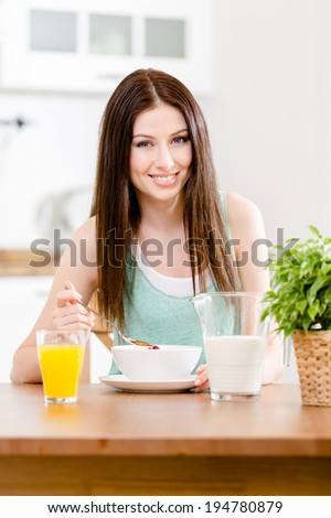Portrait of the girl eating healthy muesli with milk and citrus juice sitting at the kitchen table - stock photo