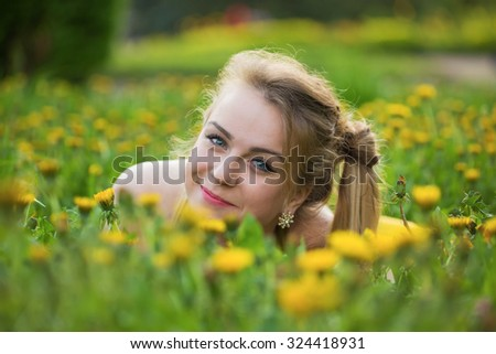 Portrait of the girl in dandelions - stock photo