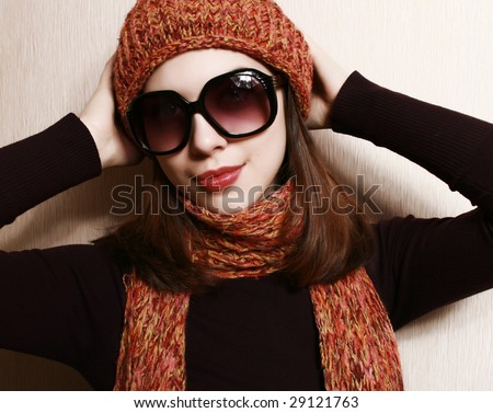 Portrait of the girl in glasses, an orange cap and a scarf.