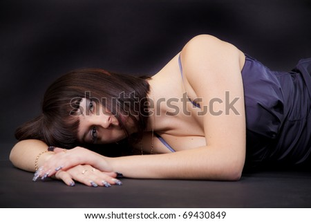 Portrait of the girl lying on a black background