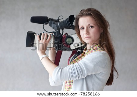 Portrait of the girl of the reporter with a videocamera with a direct sight - stock photo