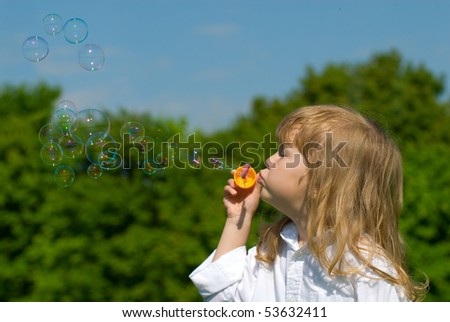 Portrait of the girl playing with soap bubbles