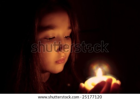 Portrait of the girl with a candle in hands. The spirituality face . Mood of sacrament and revelation. - stock photo