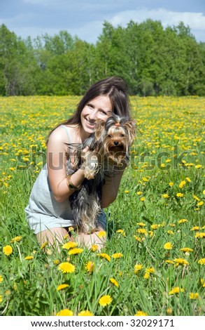 portrait of the girl with puppy in field amongst dandelion