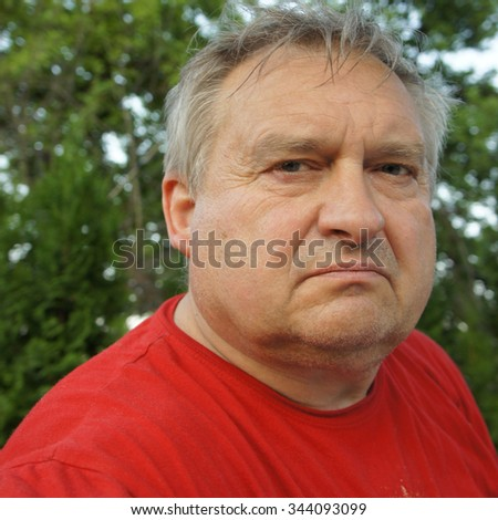 Portrait of the grey-haired elderly man in a red shirt in the summer in village on the nature