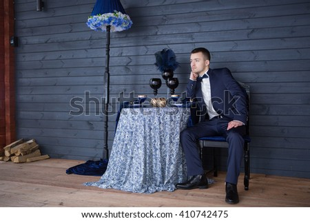 Portrait of the groom in a stylish interior. Groom sitting in a chair.