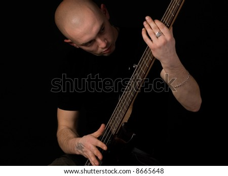 Portrait of the guitarist on a black background.