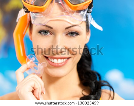 Portrait of the happy beautiful woman enjoying at beach. Pretty girl with a protective swim mask on the head. - stock photo