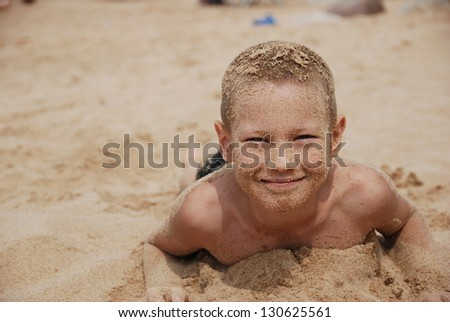 portrait of the happy boy in sand - stock photo