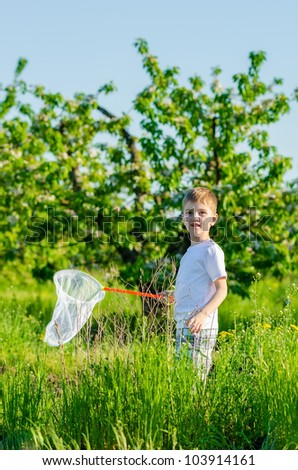 portrait of the happy boy with a net in a blossoming garden - stock photo