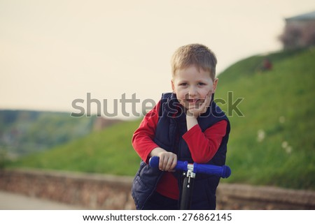 portrait of the happy child who rides the scooter in the evening - stock photo