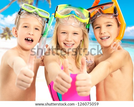 Portrait of the happy children with thumbs-up gesture at beach.  Schoolchild kids standing together in bright color swimwear with swimming mask on head . - stock photo