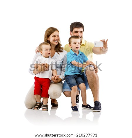 Portrait of the happy family with two children and pregnant mother taking self picture, isolated on white background - stock photo