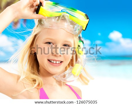 Portrait of the happy girl enjoying at beach.  Schoolchild girl with swimming mask on head.