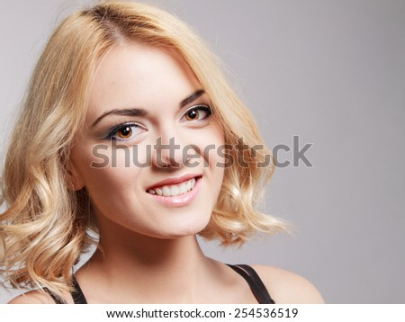 Portrait of the happy smiling girl posing in studio, on grey background. - stock photo
