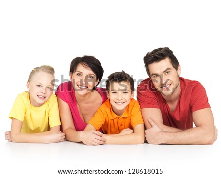 Portrait of the happy young family with two children lying at studio on white floor - stock photo