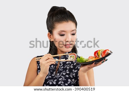 Portrait of the Happy Young Japanese Woman Eating Sushi - stock photo