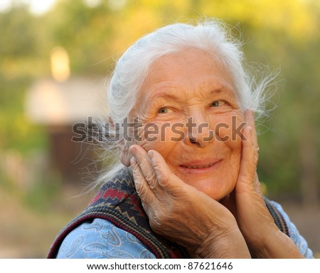 Portrait of the laughing elderly woman. A photo on outdoors - stock photo