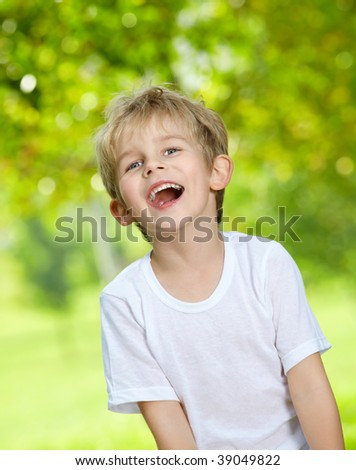 Portrait of the laughing loudly boy against a summer garden - stock photo
