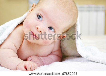 Portrait of the little baby under a terry towel - stock photo