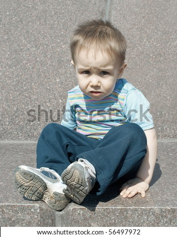 Portrait of the little boy against stone wall