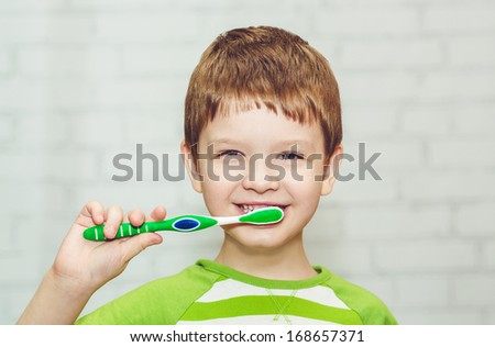 Portrait of the little boy brushing her teeth - stock photo