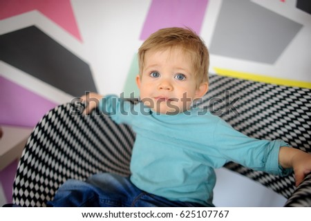 portrait little boy sitting armchair touching stock photo royalty