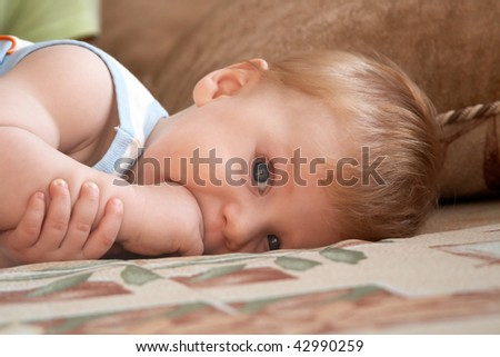Portrait of the little boy with fingers in a mouth - stock photo