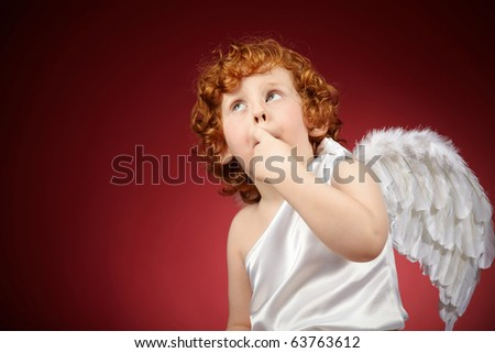 Portrait of the little boy with wings behind the back on a red background - stock photo