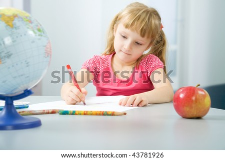 Portrait of the little girl drawing houses - stock photo