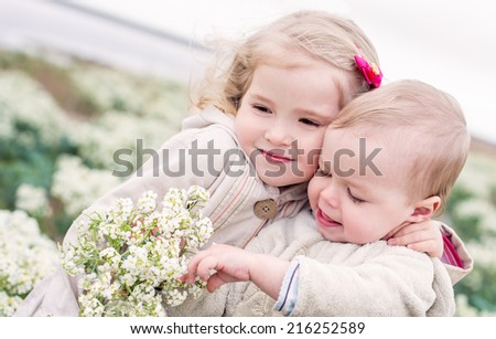 Portrait of the little sister and its toddler brother among the wildflowers - stock photo