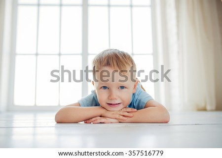 portrait of the little smiling boy lying on the floor - stock photo