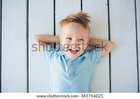 Portrait of the little smiling boy lying on the floor with his hands behind his head - stock photo