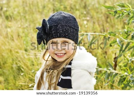 Portrait of the little smiling girl outside - stock photo