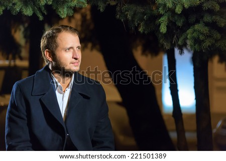 Portrait of the man in night park - stock photo