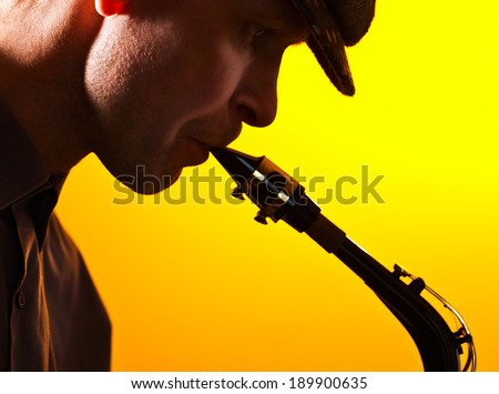 Portrait of the man playing a saxophone - stock photo