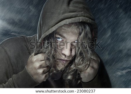 Portrait of the man under the rain. He could be assassin, thief, hitman, stranger, etc. - stock photo