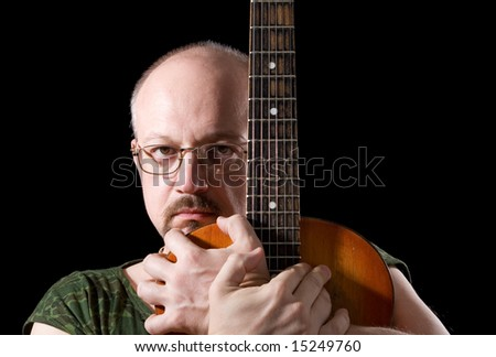 Portrait of the man with an acoustic guitar on a black background