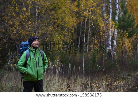 Portrait of the mature backpacker in an autumn forest - stock photo