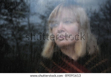 Portrait of the middle-aged woman looking through the window on a rainy day - stock photo