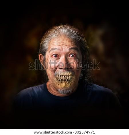 Portrait of the old man vampire on dark background - stock photo