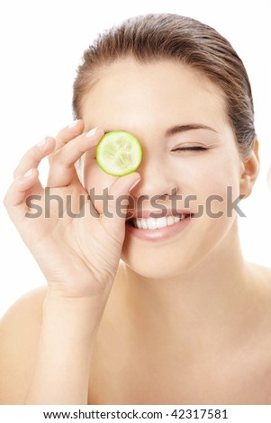 Portrait of the playful girl covering an eye by a slice of a cucumber, isolated - stock photo