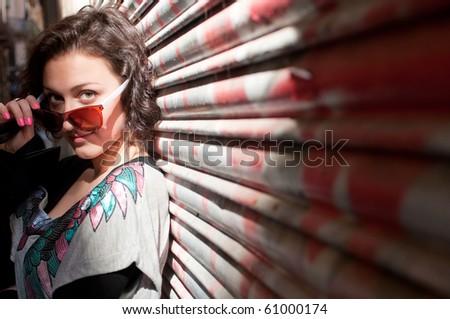 Portrait of the pretty girl near the graffiti wall - stock photo