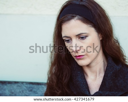 Portrait of the profile of a young brunette woman looking down and sitting on a bench outside - stock photo