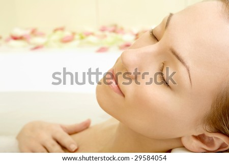 Portrait of the relaxing girl in a bath with petals of roses - stock photo