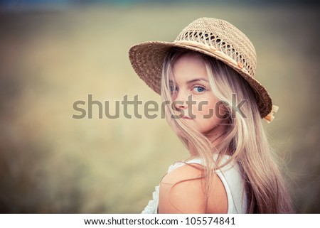 portrait of the rural girl in a straw hat - stock photo