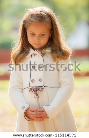 portrait of the sad girl in park - stock photo