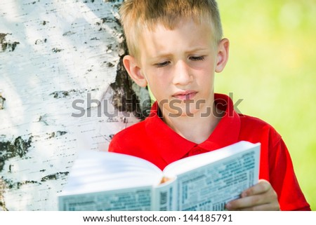 Portrait of the schoolboy reading the book at  nature