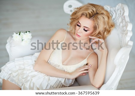 Portrait of the sensual and sexy tender blonde sitting in a white chair in the studio on a light background